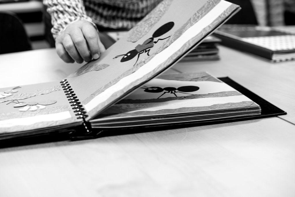 Photo d'un épais livre à anneaux où les pages sont réalisées en collages de matériaux différents.