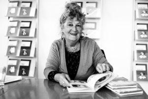 Portrait de Marie Henchoz, assise devant une table, un livre ouvert devant elle.