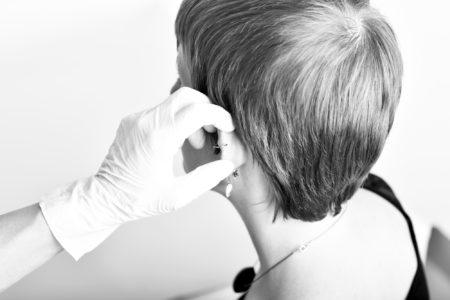 Une jeune femme se fait piercer l'oreille.