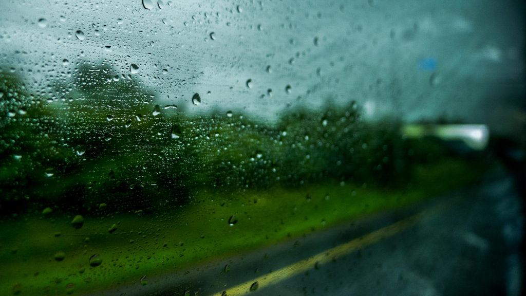 Gouttes de pluie sur une vitre de voiture, avec un paysage vert flou en arrière plan.