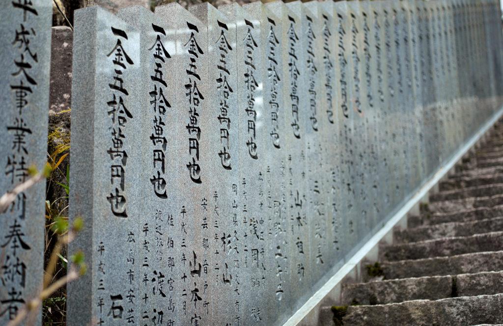Un escalier bordé de stèles de granit frappées d'idéogrammes kanji.