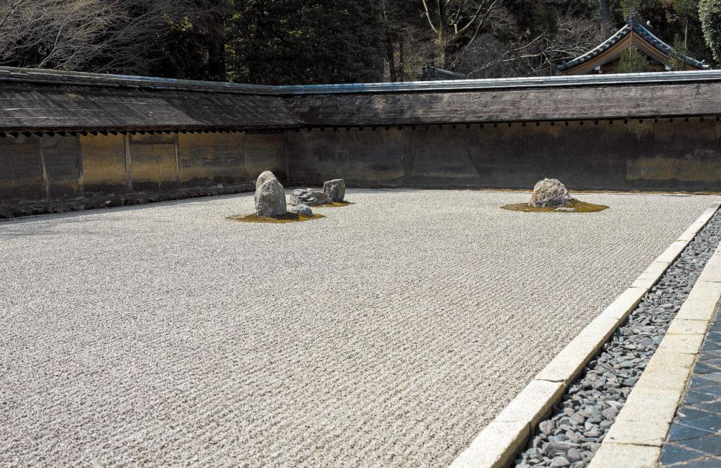 Quelques rocs granitiques au milieu d'un jardin zen en gravier ratissé entouré de haut murs.