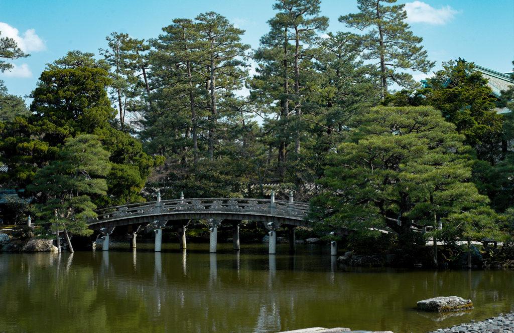 Un pont légèrement bombé enjambe un lac bordé d'arbres majestueux.