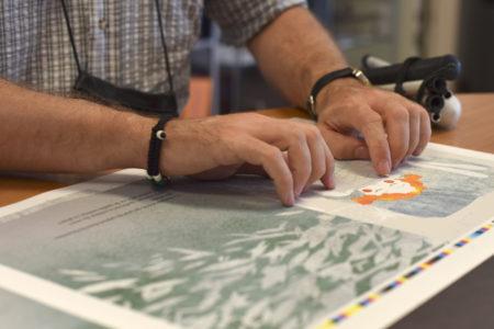 Des mains en gros plan lisent un texte en braille