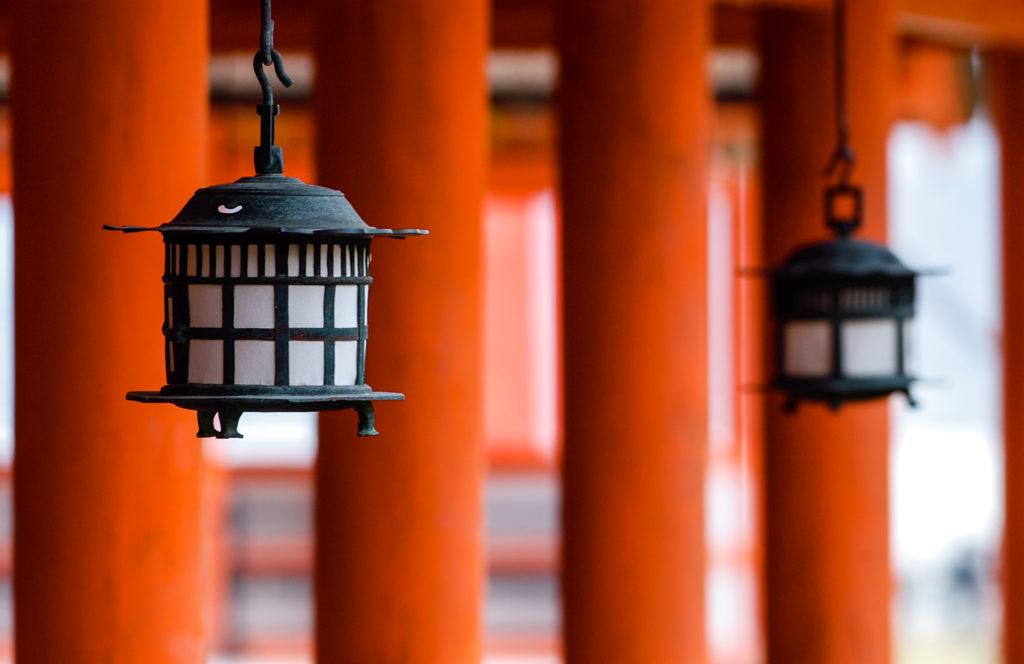 Des lanternes en fonte suspendues devant des piliers rouges évoquant un temple shinto.