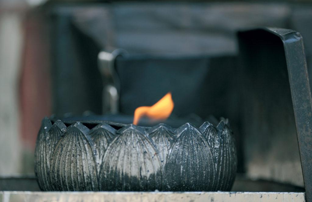 Une lampe à huile en forme de lotus brûle dans un temple de l'île de Shikoku.