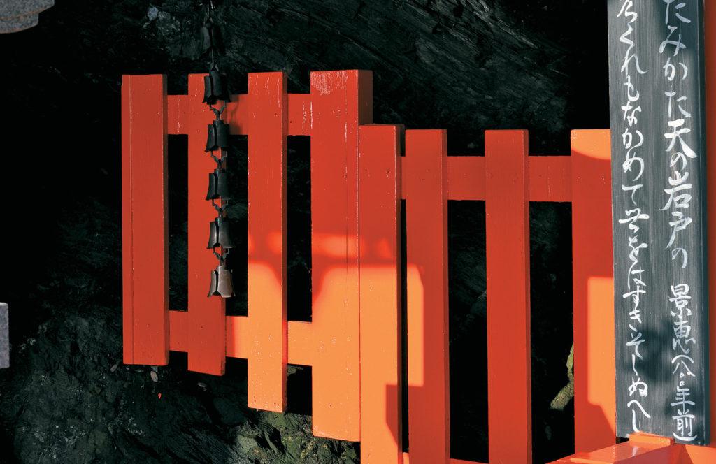 Portail orange sur le fond noir des rochers cachés dans les ombres de l'arrière-plan. Une guirlande de clochettes pend ddevant, des idéogrammes peints verticalement bordent le côté droit de l'image.