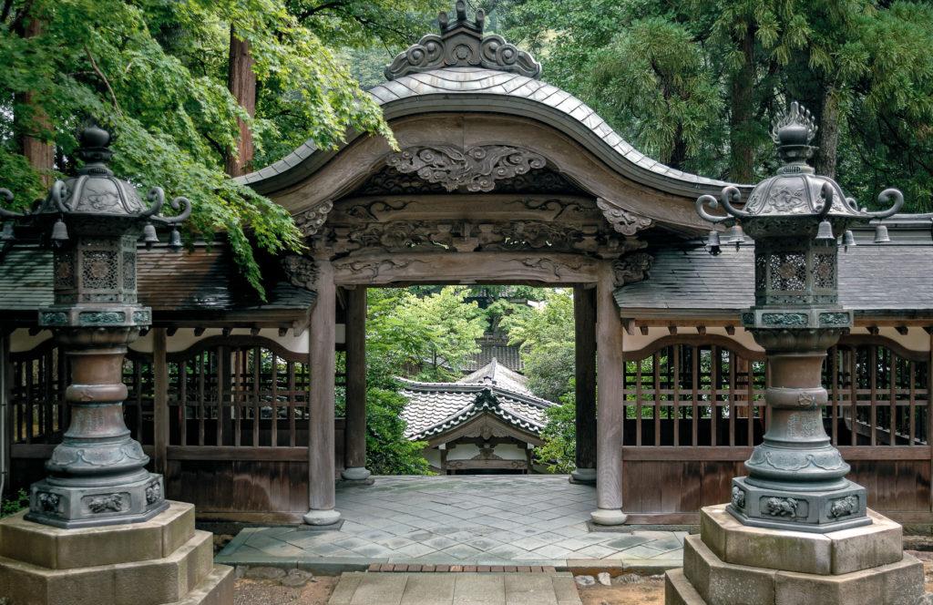 Au milieu d'une forêt verdoyante, un portique en bois travaillé mène à un temple en contre-bas.