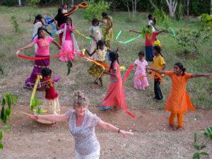 Photo de Marie Henchoz accompagnée de filles indiennes dansant avec des rubans dans la nature.