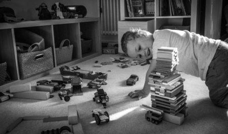 Enfant jouant dans sa chambre avec des éléments en bois.