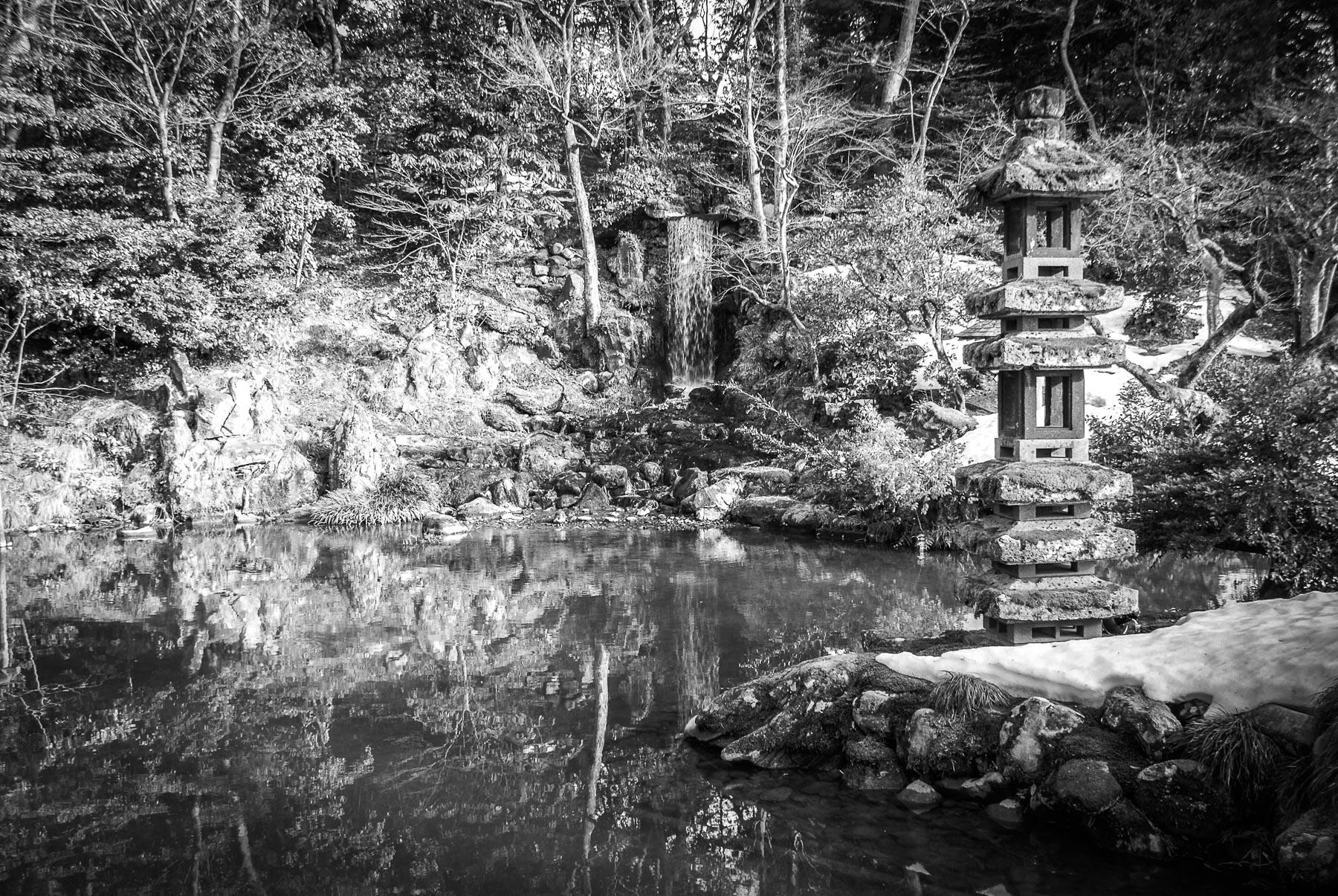 Petit lac avec cascade entouré de verdure et d'un petit temple en pierre.