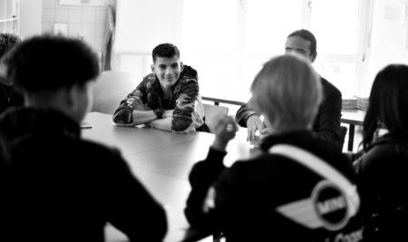 Jeunes assis autour d'une table et jouant à un jeu de cartes mathématiques.