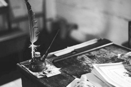 Une plume d'oiseau plantée dans un encrier sur un ancien pupitre en bois.