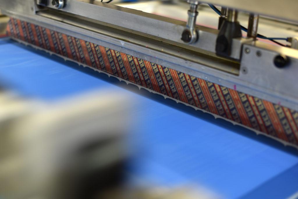 Encre passant dans les pochoirs d'une machine cylindrique (technique d'impression de la sérigraphie).