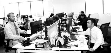 Des hommes stressés en complet-cravate de part et d'autre d'une rangée d'ordinateurs sur la table commune d'un open space.
