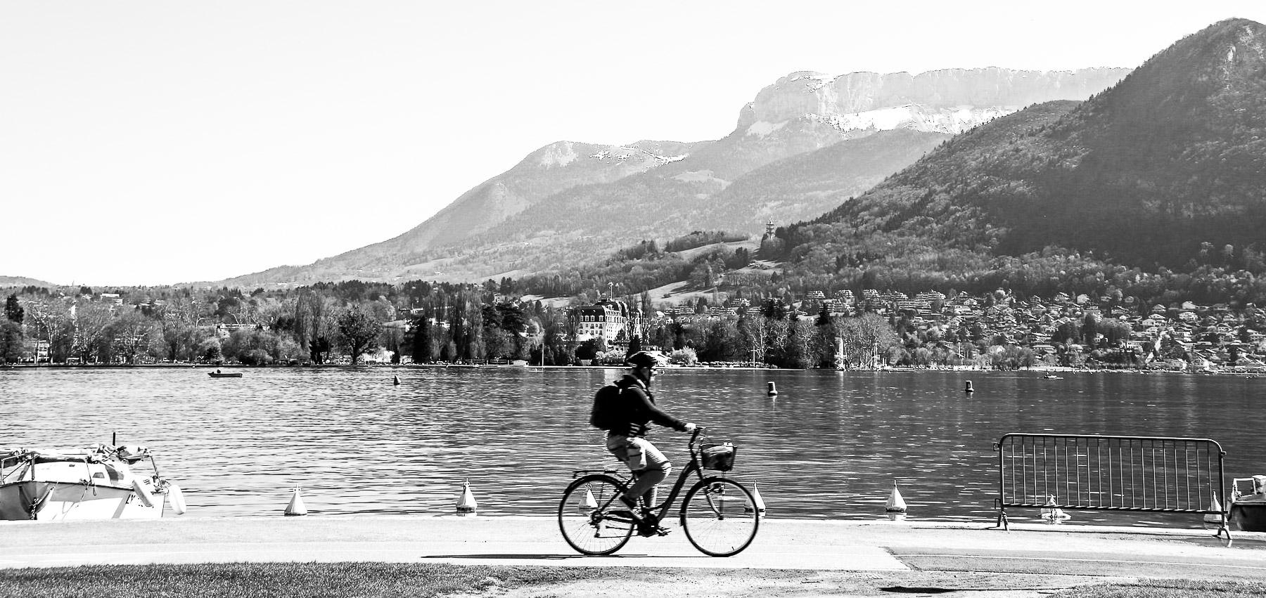 Photo d'un cycliste passant devant un lac, avec des montagnes en arrière-plan.