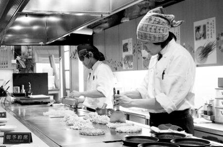 Cuisiniers préparant des okonomiyaki dans un restaurant japonais