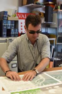 Julien Conti, non-voyant de naissance, teste le rendu de l'impression en braille chez le sérigraphe.