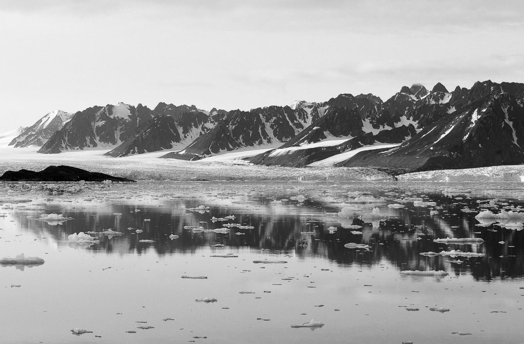 Photo de montagnes enneigées derrière un lac sur lequel flotte de la glace.